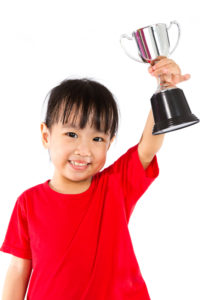 Asian Little Chinese Girl Smiles with a Trophy